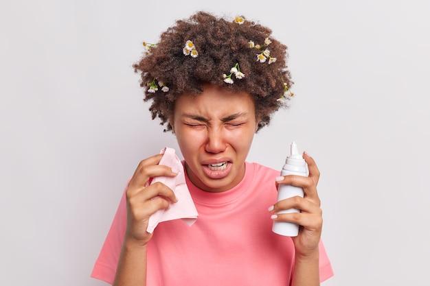 Женщина использует назальный спрей, удерживает ткани, чувствует себя плохо, страдает от аллергического ринита, чихает, постоянно изолирована на белом