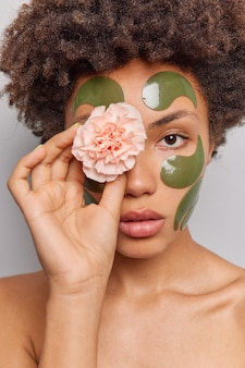 Woman uses natural beauty products holds flower on eye applies collagen green patches on face stands shirtless poses indoor