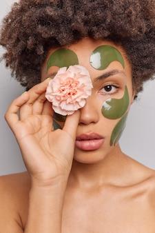 여자는 자연 미용 제품을 사용하여 눈에 꽃을 들고 얼굴에 콜라겐 녹색 패치를 적용합니다. 셔츠를 입지 않은 실내 포즈