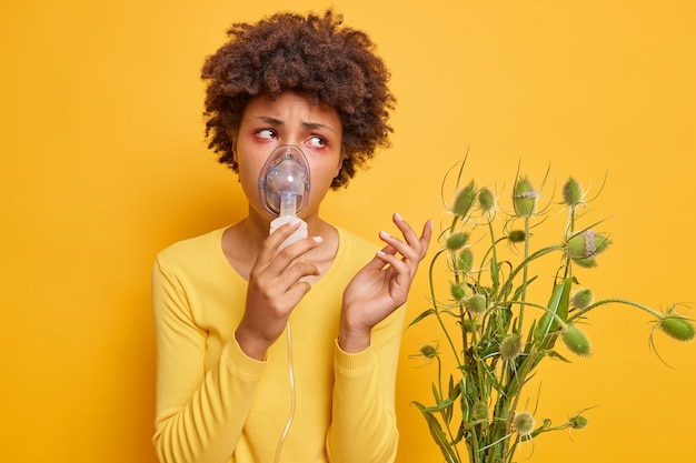 女性はアレルギー治療にネブライザーを使用しています野生の花にアレルギーのある喘息発作があります黄色に分離された吸入マスクを着用しています