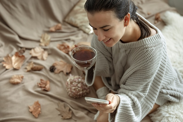 A woman uses the phone and holds a cup of tea while sitting in bed in a cozy knitted sweater