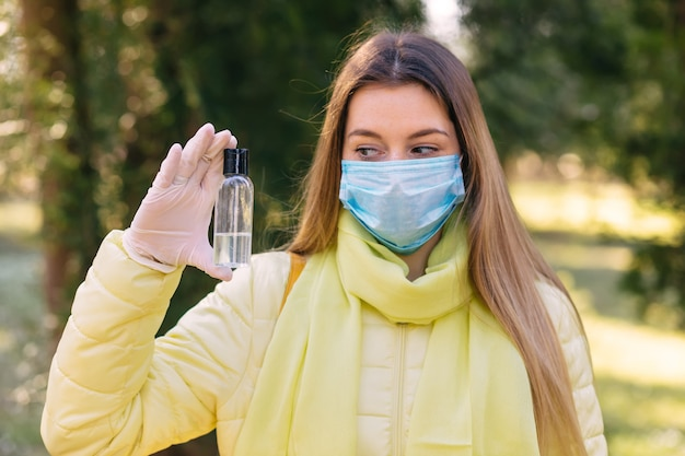 A woman uses a spray in her hand to disinfect hands. she wears a medical protective face mask, means of protection against the virus. covid-19