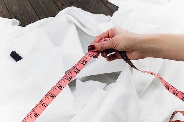 女性は白い布で働くテープ測定を使用します