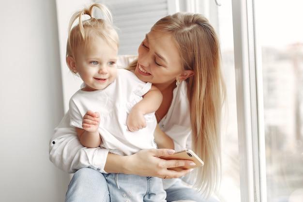 女性は電話を使います。白いシャツを着たお母さんが娘と遊んでいます。家族は週末に楽しんでいます。