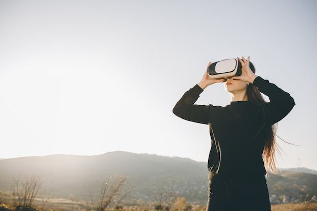 Woman uses virtual reality glasses at sunset. evening time, twilight. relax, entertainment and technology concept