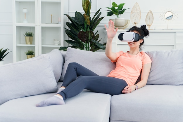 女性はソファで自宅でvrゴーグルを使用します。未来のテクノロジー。