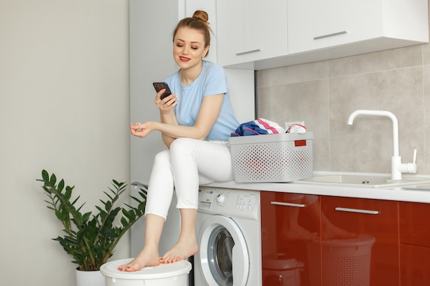 Woman uses a washing machine in the kitchen