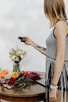 카메라를 사용하여 형형색색의 꽃 사진을 찍는 여성