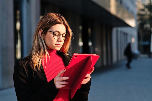 屋外に立っているときにデジタルタブレットを使用している女性。