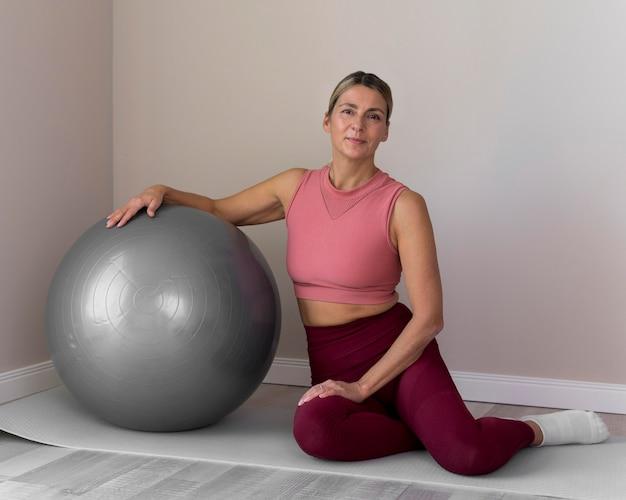 Женщина с фитнес-мячом для ее упражнений