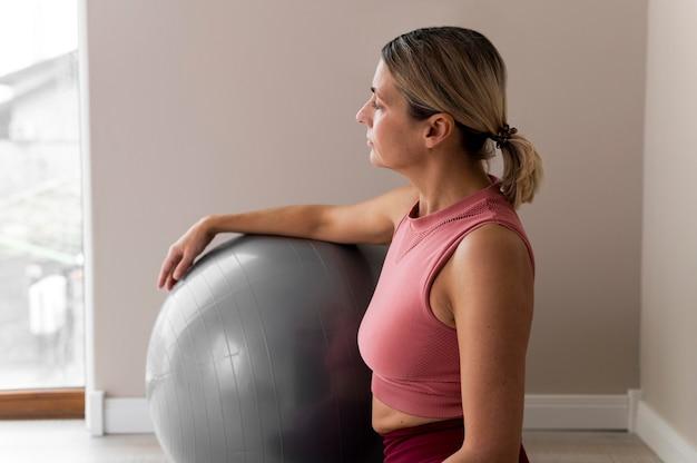 彼女のトレーニングにフィットネスボールを使用している女性