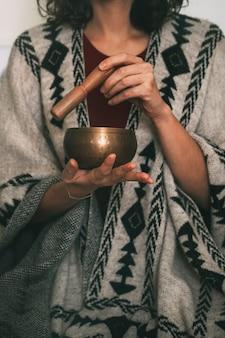 手作りのポンチョコピースペース垂直に身を包んだ瞑想で金色のチベットのボウルを使用している女性