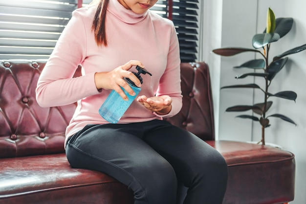 Женщина использует дезинфицирующее средство для рук спиртовой гель, чтобы вымыть руки, чтобы предотвратить вирусы и болезни в домашних условиях