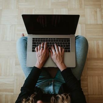 コロナウイルスの発生時に在宅勤務中にラップトップを使用している女性