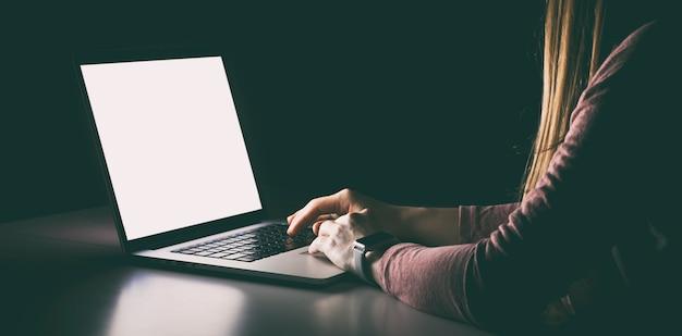 空白の画面でノートパソコンを使用している女性