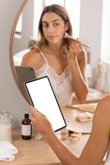 거울에 메이크업 브러쉬를 사용하는 여자