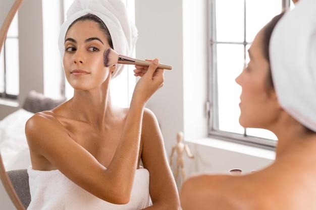 Женщина с помощью кисти для макияжа