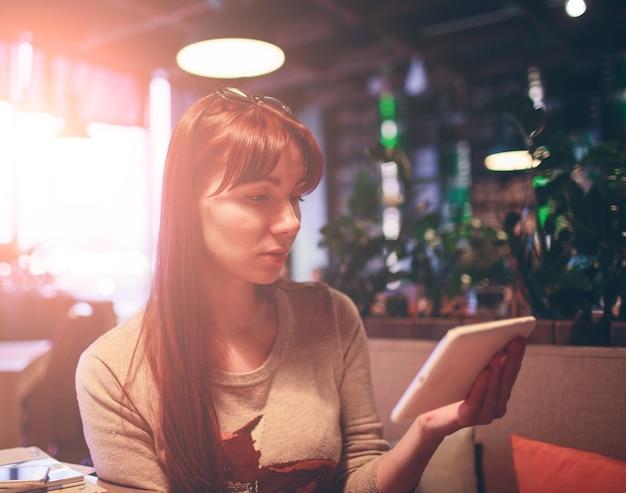 Женщина с помощью мобильного телефона в ресторане, кафе, баре