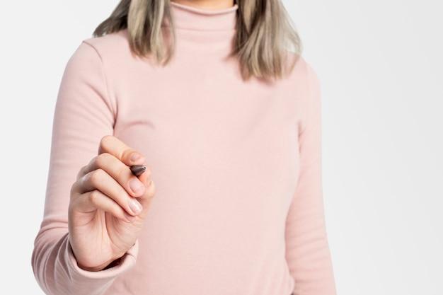 펜을 사용하고 보이지 않는 화면에 글을 쓰는 여성