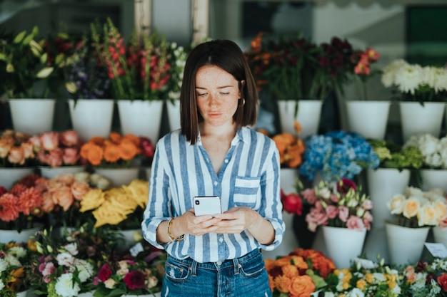 꽃집 앞에서 전화를 사용하는 여자