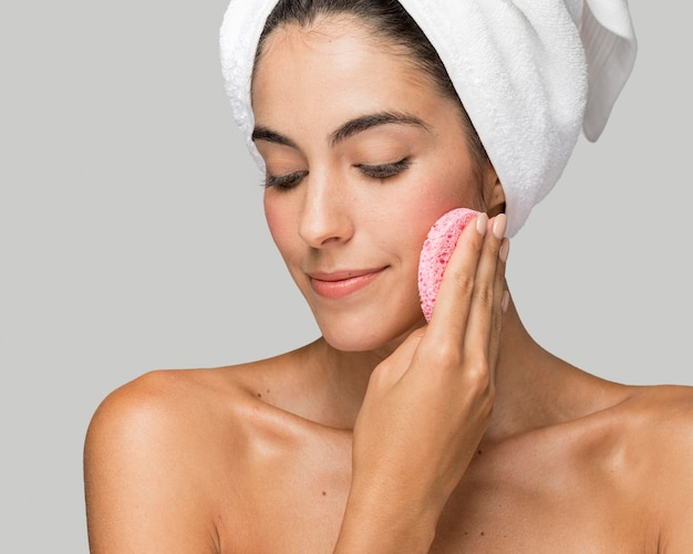 ピンクのスポンジを顔に使っている女性