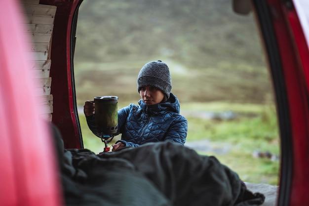 휴대용 캠핑 스토브를 사용하여 물을 끓이는 여성