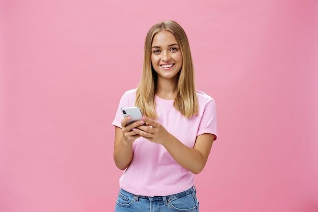 ピンクの壁に携帯電話を保持しているカメラで元気に笑っているスマートフォンを使用している女性