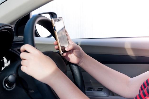 ソーシャルメディアの常習者であるため、車の運転中にスマートフォンを使用している女性