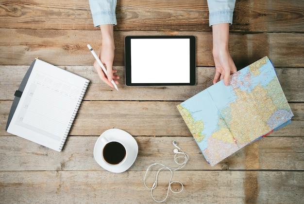 世界地図と彼女の隣にコーヒーカップを備えたデスクトップでタブレットpcを使用している女性。彼女は鉛筆を持っています