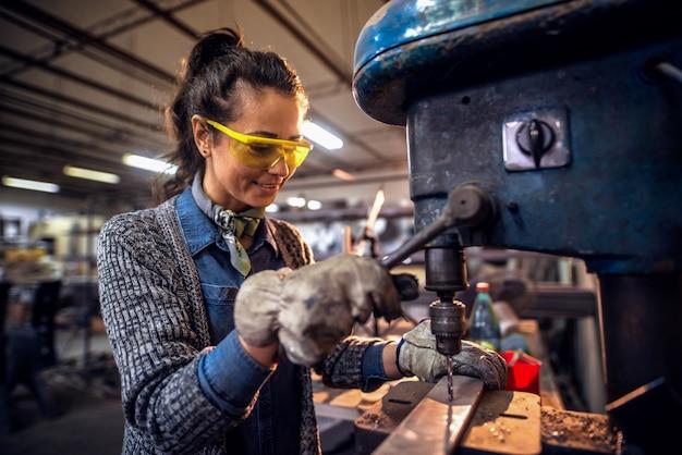 워크샵에 서있는 동안 수직 기계를 사용하여 금속에 구멍을 만드는 여자