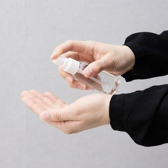 細菌やウイルスの蔓延を防ぐために手を掃除するためにボトルにアルコールスプレーを使用している女性。感染症における衛生と安全。
