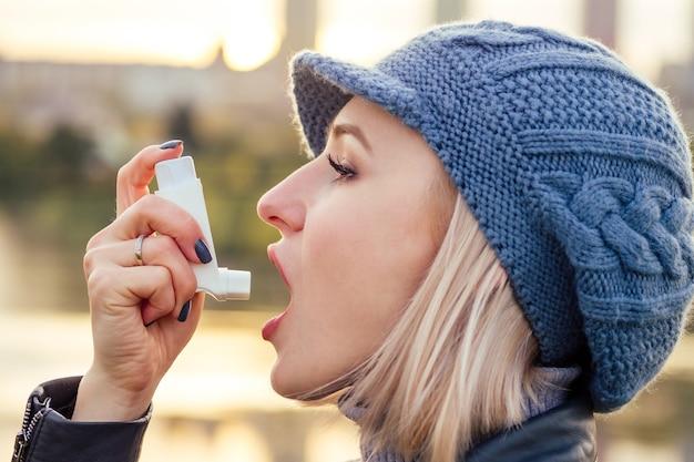 寒い冬の秋の公園で喘息吸入器を使用している女性