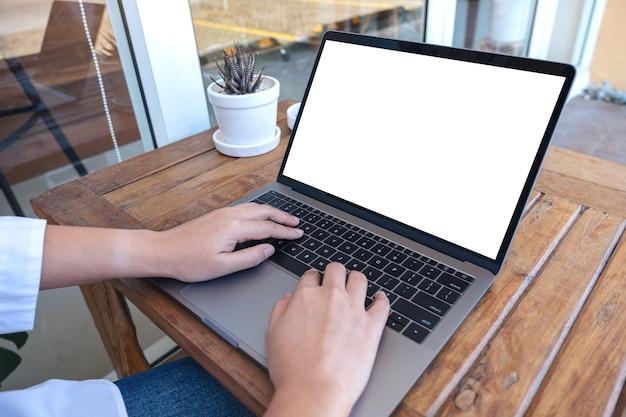 여자를 사용하고 공원에 앉아 빈 흰색 화면 노트북에 입력