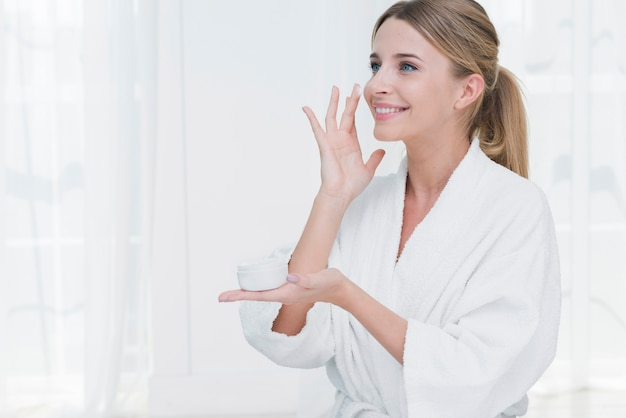 Woman using beauty cream in a spa