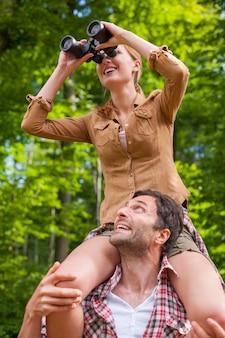 숲에서 쌍안경을 사용하는 여자
