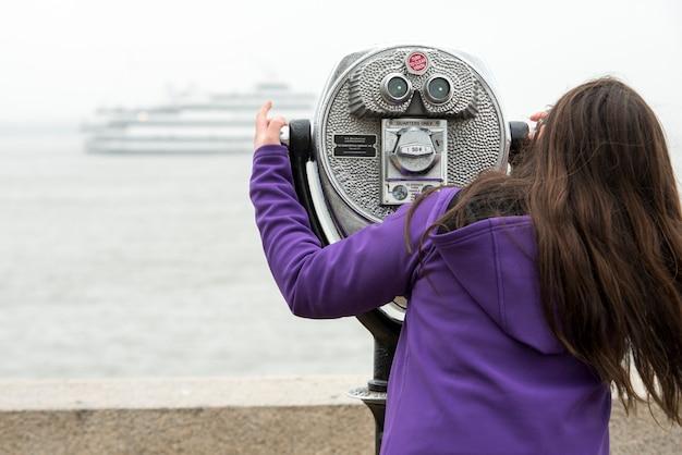 Woman using binoculars at upper new york bay, ellis island, jersey city, new york state, usa