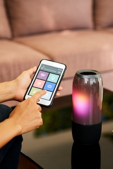 Woman using bluetooth to connect with wireless speaker