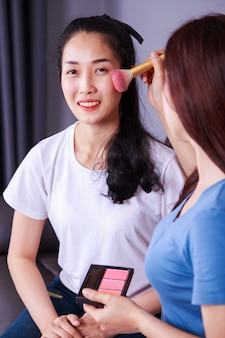 Woman using brush makeup on face her friend