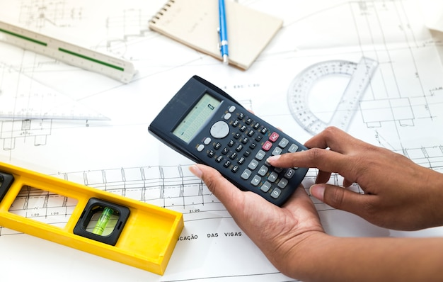 Woman using calculator near plan and equipments