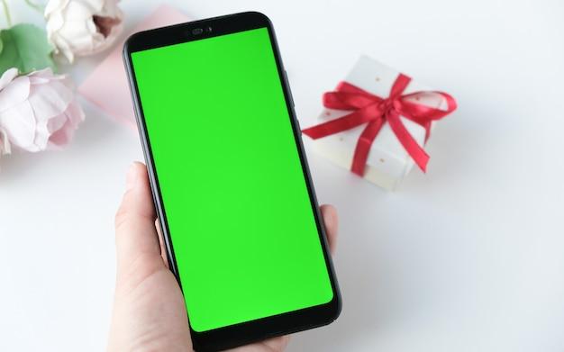 緑の画面で携帯電話を使用している女性