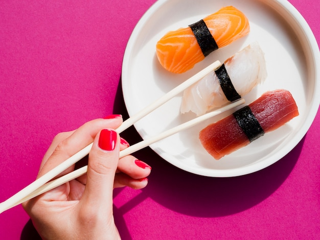 Woman using chop sticks to pick a sushi from plate