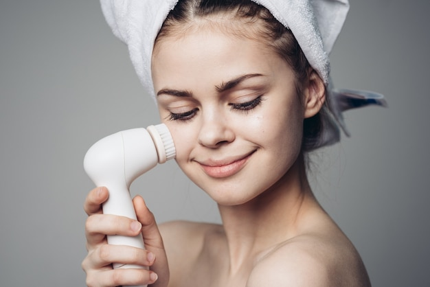 Woman using a cleansing face massage brush