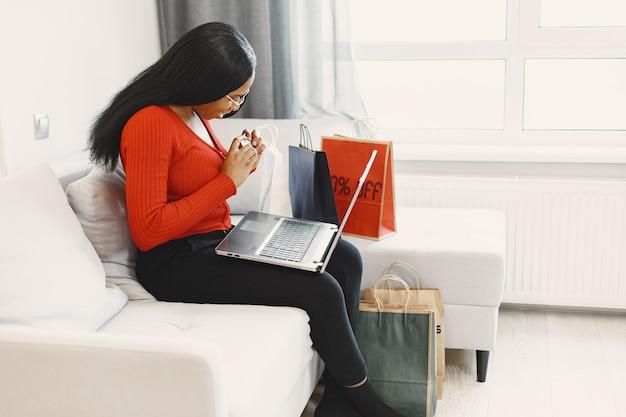 Женщина, использующая компьютер и кредитную карту
