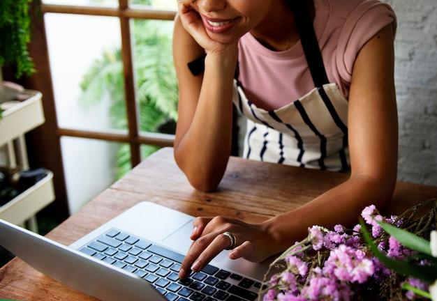 Женщина, использующая компьютерный ноутбук в цветочном магазине
