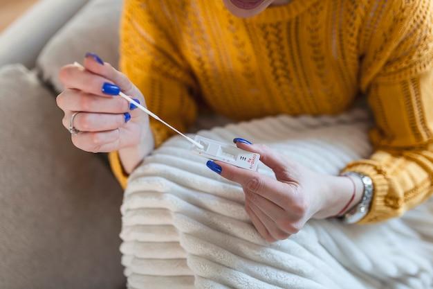 自宅でコロナウイルスpcr検査をしながら綿棒を使用している女性。コロナウイルス迅速診断検査を使用している女性。 covid-19の鼻腔スワブを使用して自宅で若い女性。