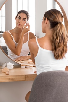 Woman using cream and looking into mirror self care concept