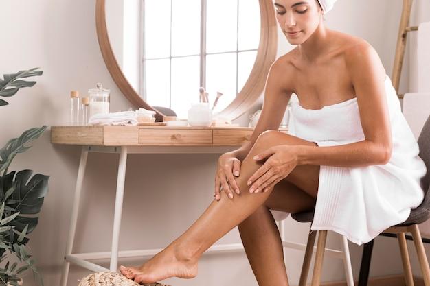 Женщина, используя крем на ногах