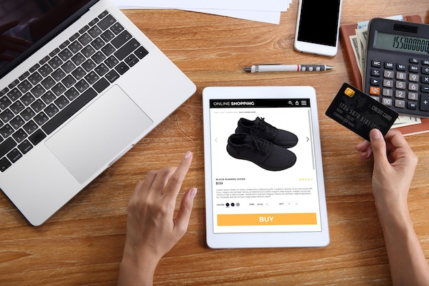 Woman using credit card for buy black running shoes on ecommerce website via tablet with laptop, smartphone and office stationery on wooden desk