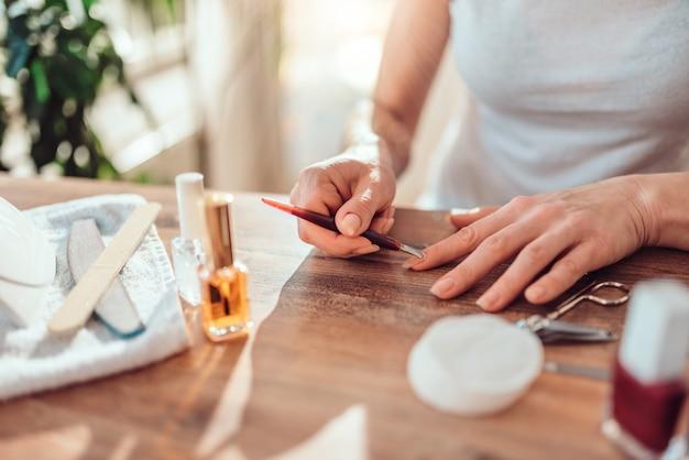 Woman using cuticle pusher