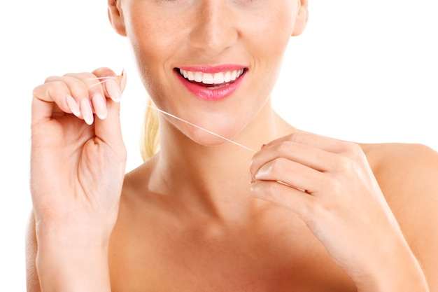 Woman using dental floss over white background